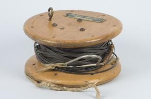 steel surveyor's tape on wooden spool