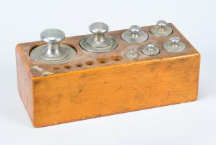 set of weights in a wood tray