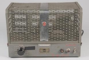Audio instrument, amplifier. Rectangular, grey metal deivice with grate-like top with a silver strip down the center. Black dial, red and black buttons and switch.