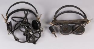 two headphones removed from green wooden storage box containing  headphones