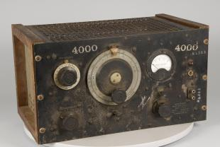 Audio instrument, oscillator. Large rectangular body, wood frame on sides, black front panel and decorative grill on to pand back. On front panel, large dials, circular window for meter, pair of electrical connectors, indicator light and switches.